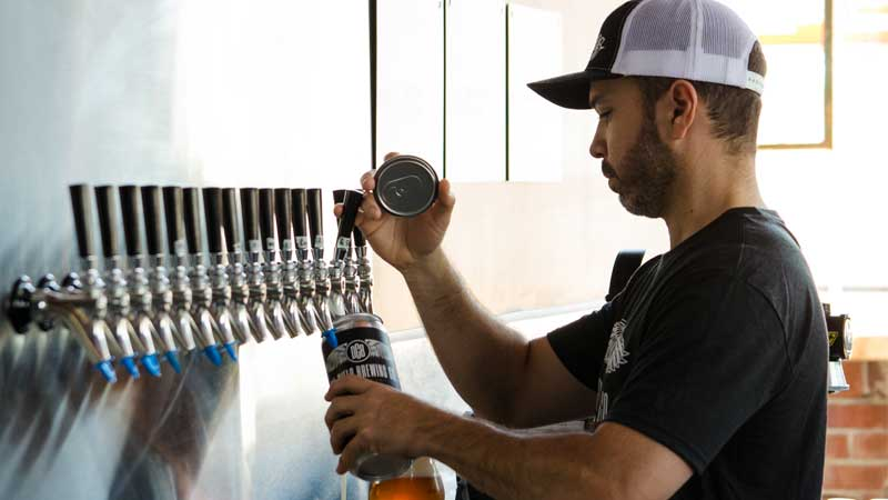 Owner of Del Cielo Brewing Co. Luis Castro filling up a crowler at his taproom in Martinez, California.